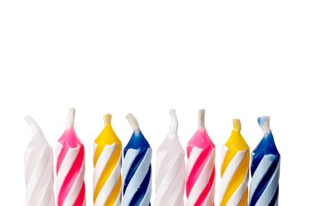 Horizontal close up of birthday candles on white