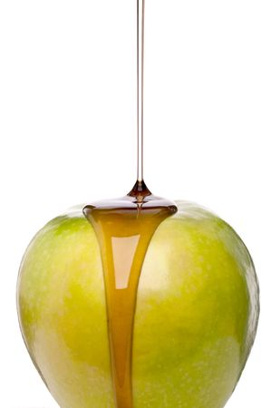 Maple syrup being poured on a green apple on white