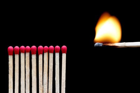 A burning match near other matches on black