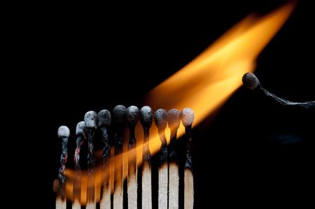 A group of burning matches on black