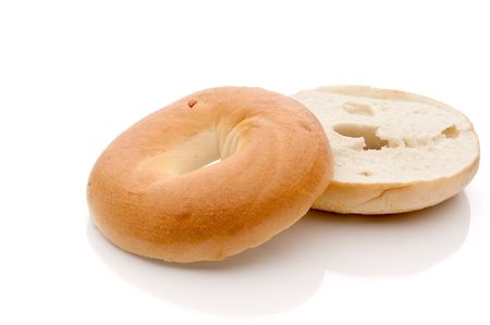 a horizontal sliced bagel on a white reflective surface