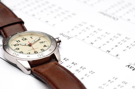 A wristwatch on a calendar