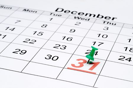Horizontal image of a calendar with New Year's day marked with a green tack