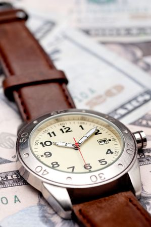 Vertical image of a wristwatch on American currency