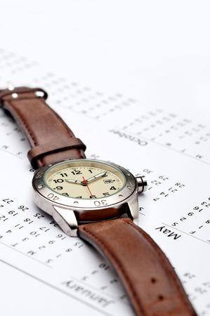 Vertical image of a wristwatch on a calendar