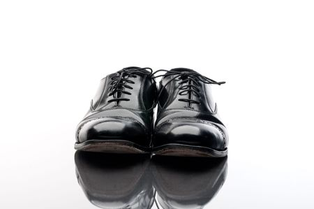 Black leather business shoes on a reflective surface