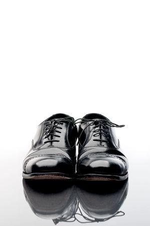 Zapatos de negocio de cuero negro sobre una superficie reflectante