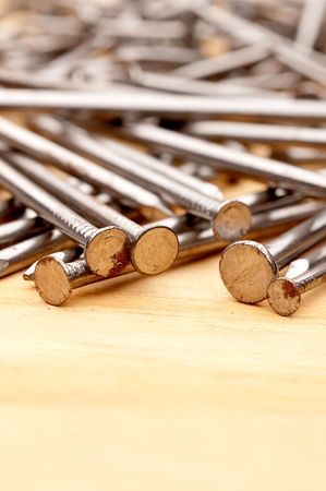 Vertical close-up of construction nails on wood
