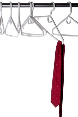 A burgundy tie on a hanger attached to a closet pole