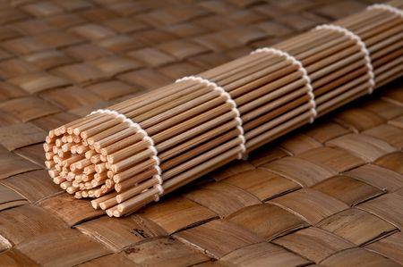 Sushi rolling mat on a woven Bamboo place mat