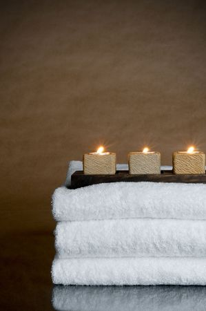 Three candles on three spa towels Stock Photo