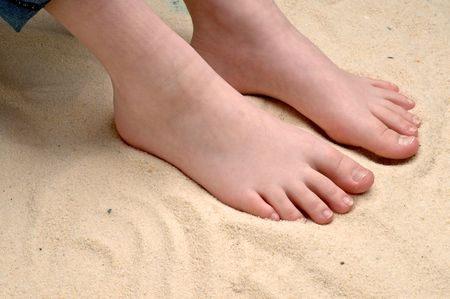 horizontal image of a childs feet in the sand Stock Photo