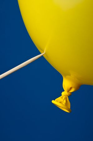 a pointed stick ready to pop a yellow balloon on blue Imagens