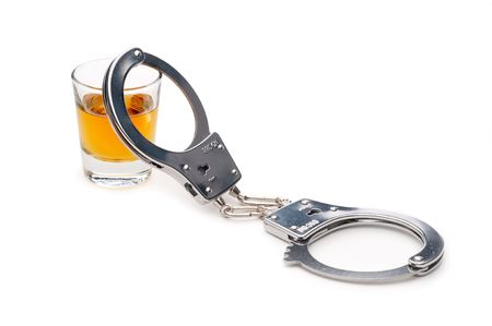 locked: A drink and handcuffs, addiction or alcoholism