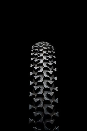 Vertical close up of a mountain bike tire on black