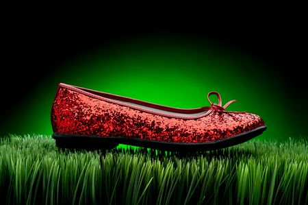 Sequined red slipper on green grass against a fading green background Stock Photo - 6410720