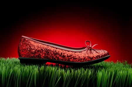 fading: Sequined red slipper on green grass against a fading red background
