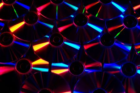 An array of computer CDs under colored lights Imagens