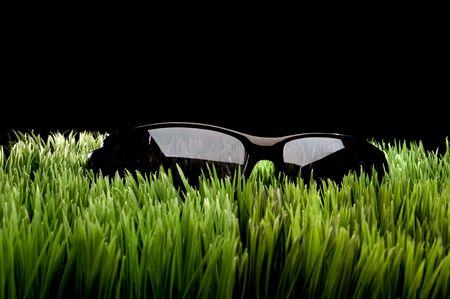 Black framed sunglasses on grass against black Imagens