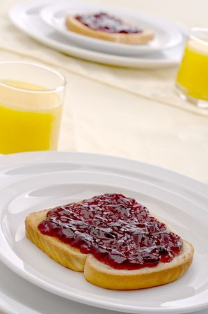 Morning breakfast with orange juice and jam or jelly on toast
