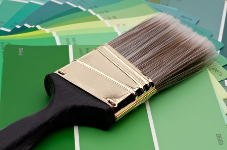 horizontal close up of a paint brush on green paint samples