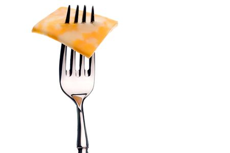 A horizontal image of a slice of marbled cheese on a silver fork on white with copy space to the right