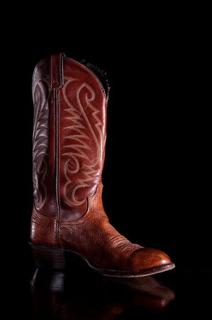 Vertical image of a brown leather cowboy boot on a reflective surface Imagens