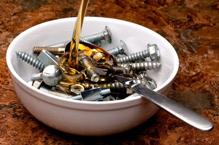Horizontal image of oil being poured onto a breakfast seving of nuts and bolts
