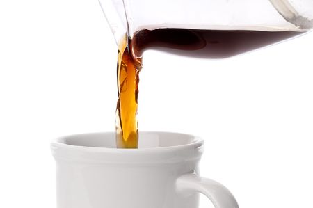 close up of coffee being poured into a coffee cup on white Imagens
