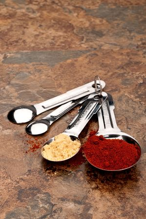 Measuring spoons with red and yellow spices on a kitchen counter