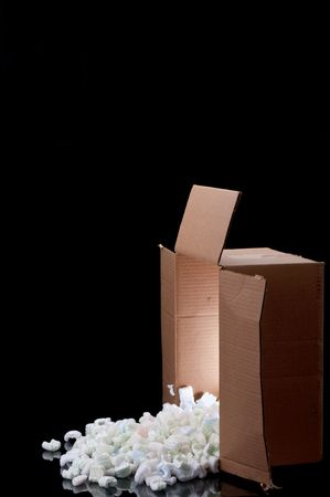 a shipping box with  a glow inside spilling peanuts on a black surface Stock Photo - 6622543