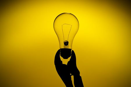 a silhouette of a clear light bulb held in a grip on a yellow glow background Imagens