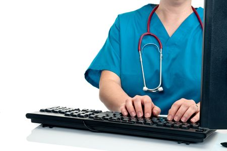 A female nurse/doctor entering data on a computer on white Imagens