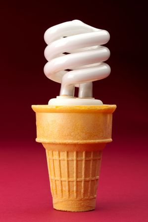 a compact fluorescent bulb in an ice cream cone on red Imagens