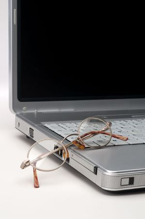 Reading eye glasses on a laptop computer on white Imagens
