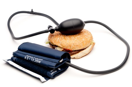 Blood pressure cuff and hamburger on white - health Imagens