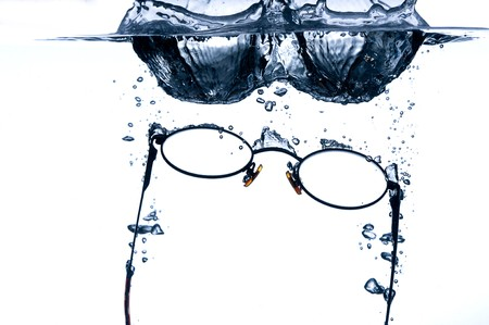 Eyeglass splashing in to water with a hint of blue Stock Photo