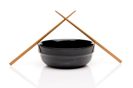 Crossed chopsticks on a black bowl on white