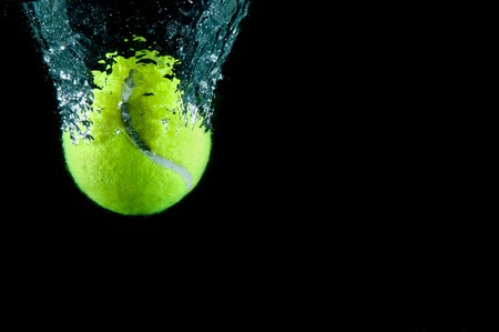 Tennis ball speeding through water on black Stock Photo