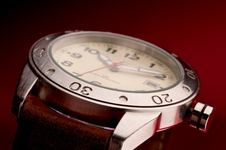 Shallow focus macro of a mans wristwatch with a red background