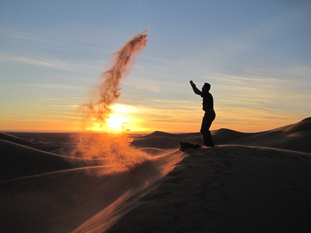 tosses: A man on a sand dune tosses sand that gets carried away in the wind in Sonora, Mexico.