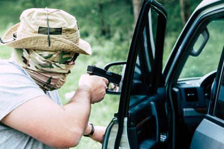 Hombre con una pistola abre la puerta del coche