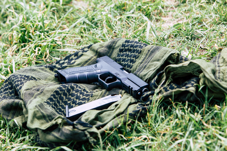 9mm ammo: A pistol with a magazine on a green background