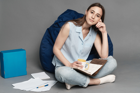 cushioned: Woman sitting on a pillow bag and holding a notebook in hands. Isolated on gray background.