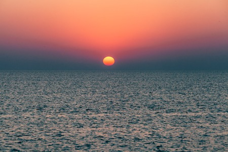 visible: Dawn or sunset on the sea, the ocean, the lake. Beautiful view. The sun is visible.