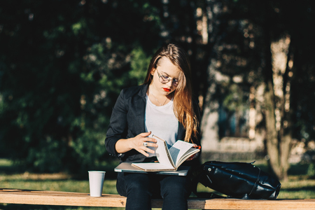 Young business woman working in the park, drinking coffee and browsing through her notebook