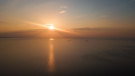 Dawn on the sea. The warm sun rises above the water. Photographed from the drone. Aerial photo shooting