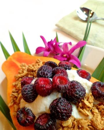 Papaya with yogurt and black raspberry as a tropical breakfast