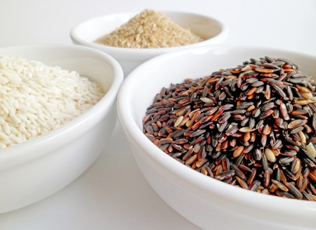 Three bowls of black rice, brown rice, and white rice with close-up focus on black rice bowl photo