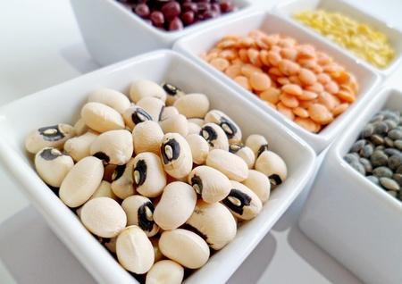 leguminosas: Primer plano de frijol mungo, el guisante de ojo negro, frijol adzuki rojas, lentejas rojas, y la lenteja verde en cuencos blancos